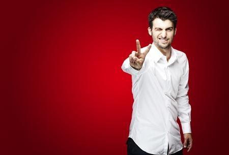 simbolo della pace: Ritratto di giovane uomo bello fare buon simbolo su sfondo rosso