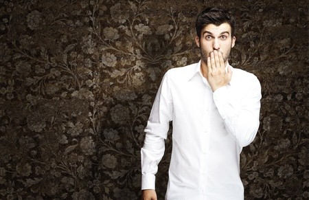 wall covering: portrait of young man covering his mouth against a vintage wall Stock Photo