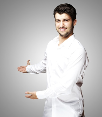 portrait of a handsome young man gesturing welcome over grey photo