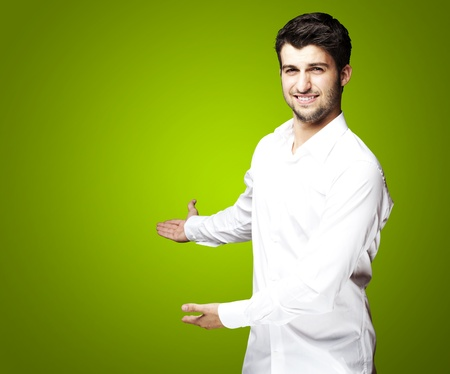 portrait of a handsome young man gesturing welcome over green