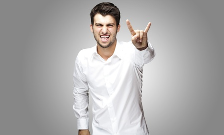 portrait of young man doing a rock and roll symbol over grey background photo