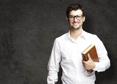 portrait of young student holding books against a grunge background photo