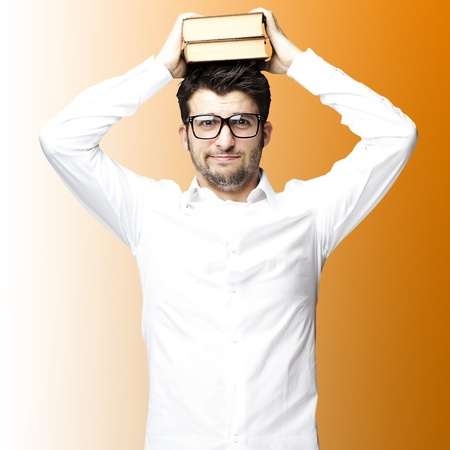 confused man: portrait of young man with glasses holding books on his head over orange background Stock Photo