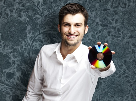 portrait of a handsome young man holding cd against a vintage wall Stock Photo - 12105393