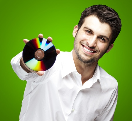 round face: portrait of a handsome young man holding cd against a green background