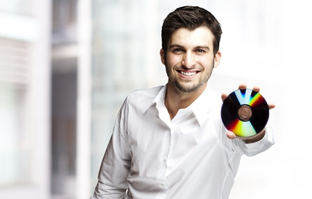 portrait of a handsome young man holding cd indoor photo