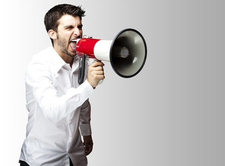 portrait of young man shouting with megaphone against a grey background photo