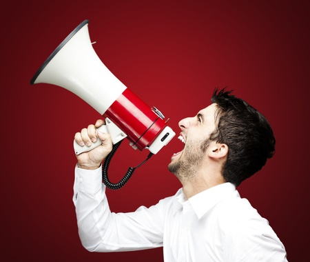 portrait of young man handsome shouting using megaphone over red background photo