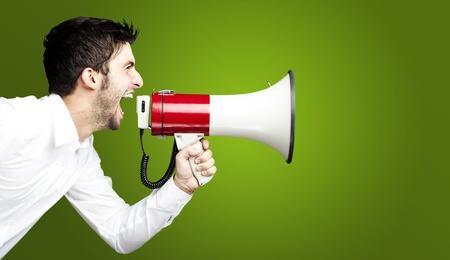 Portret van een jonge man, knappe schreeuwen met een megafoon over groene achtergrond Stockfoto
