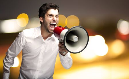 portrait of angry young man shouting with megaphone at a city by night Stock Photo - 12105191