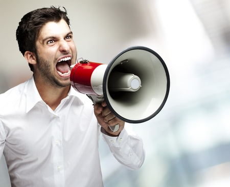 portrait of young man screaming with megaphone against a abstract background photo