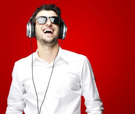 portret van een knappe jonge man luisteren naar muziek met een hoofdtelefoon over rode achtergrond