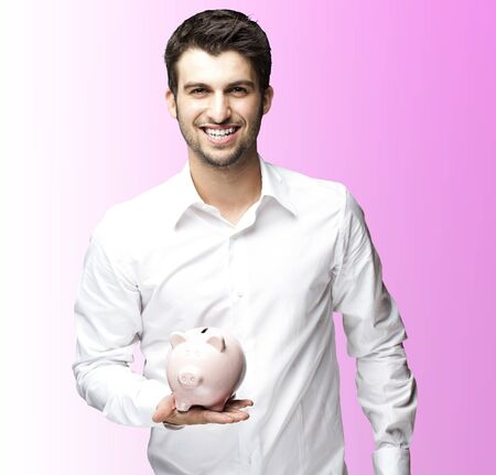 portrait of young man smiling and holding a piggy bank against a  pink background photo