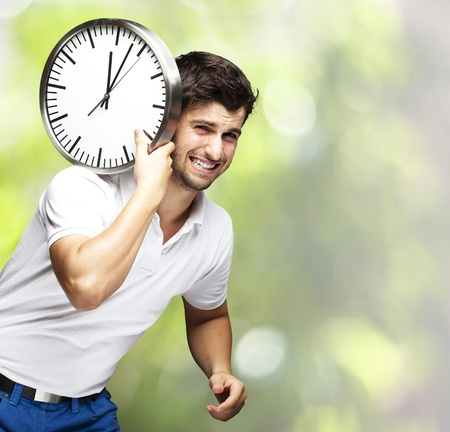 man carrying clock on his back photo