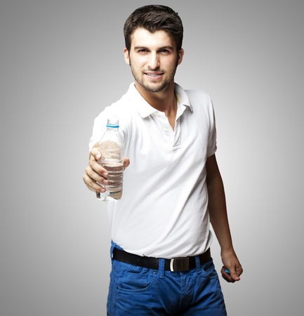 giving season: portrait of a handsome young man offering a water bottle over grey background Stock Photo