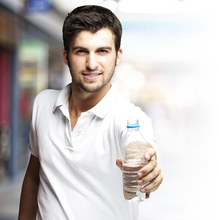 crowd happy people: portrait of a handsome young man offering a water bottle at crowded place Stock Photo