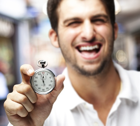 portrait of young man holding a stopwatch at a crowded place photo