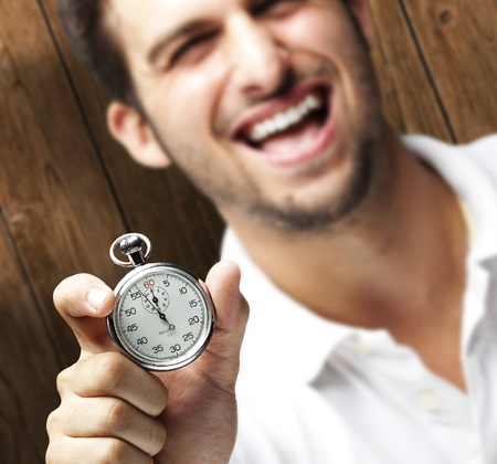 portrait of young man holding a stopwatch against a wooden wall photo
