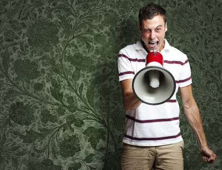 portrait of young man shouting with megaphone against a vintage background photo