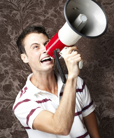 portrait of young man shouting with megaphone against a vintage wall photo