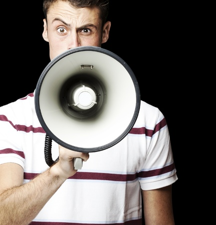 portrait of young man shouting using megaphone over black background photo
