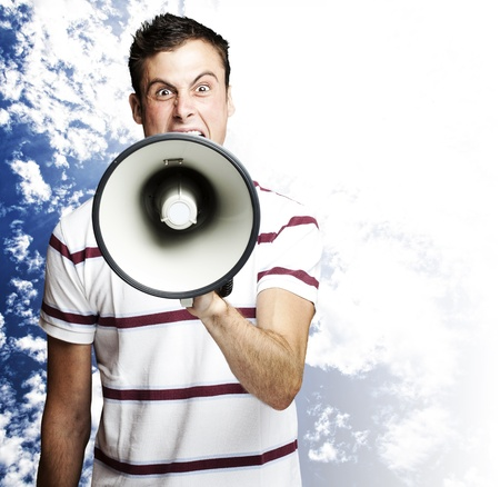 portrait of young man shouting using megaphone against a blue sky background photo