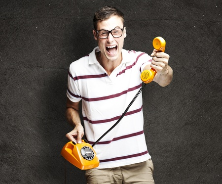 portrait of young man offering vintage telephone to call against a grunge background photo