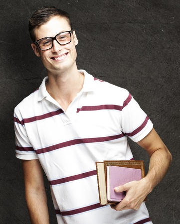 portrait of young student with glasses holding a book against a grunge background photo