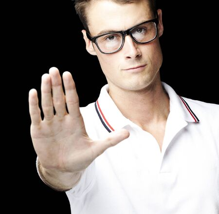 portrait of young man doing stop symbol over black background photo