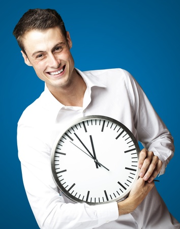portrait of young man holding clock against a blue background photo