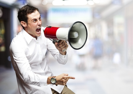 portrait of young man screaming with megaphone against a crowded place photo