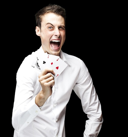 portrait of crazy man showing poker cards against a black background Stock Photo - 12105700