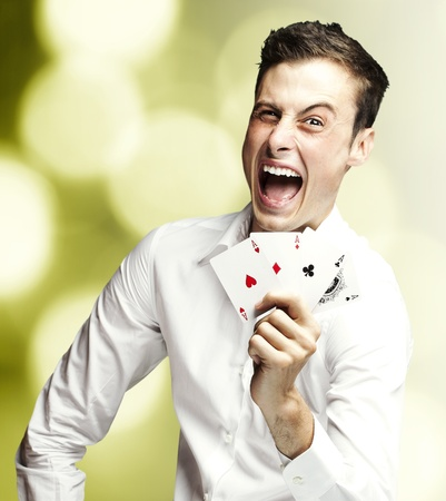 game of chance: portrait of young man showing poker cards against a abstract background