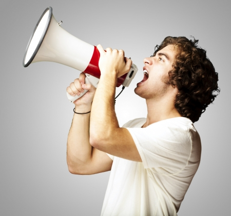 comunicar: retrato de un apuesto joven con megáfono gritando contra un fondo gris