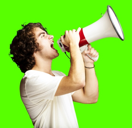 portrait of a handsome young man shouting with megaphone against a removable chroma key background photo