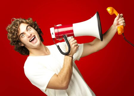 portrait of young man shouting with megaphone and talking on vintage telephone over red photo