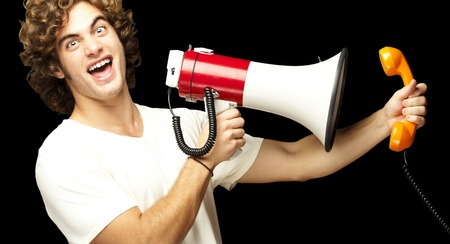 portrait of young man shouting with megaphone and talking on vintage telephone over black photo
