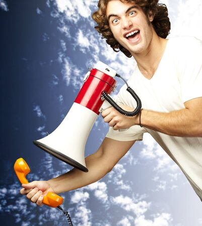 portrait of young man shouting with megaphone and talking on vintage telephone against a cloudy sky background photo