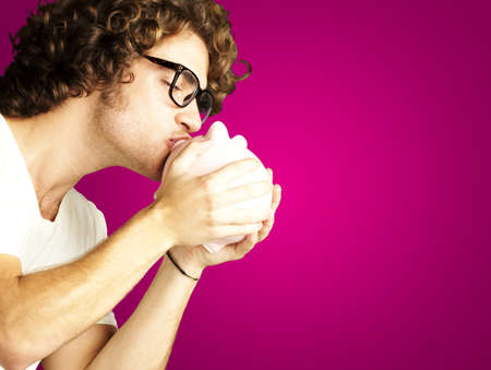 portrait of young man kissing a piggy bank against a pink background photo