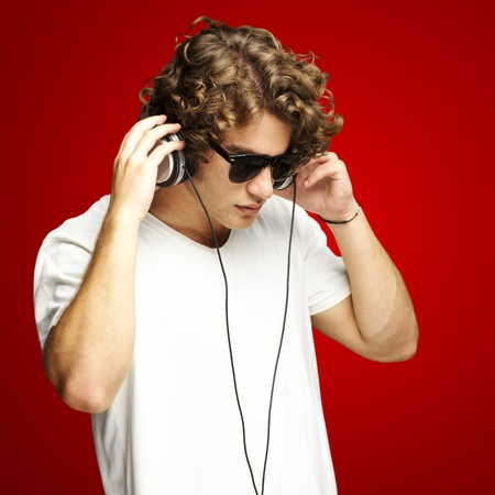 portrait of a handsome young man listening music against a red background photo