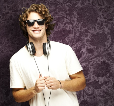 portrait of young man smiling with headphones against a vintage wall photo