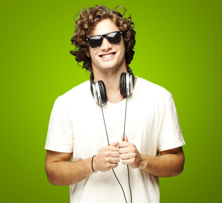 'teenager boy: portrait of young man smiling with headphones over green background Stock Photo