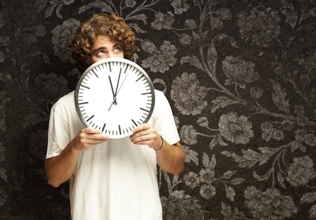 scared young man hidden behind a clock against a vintage wall Stock Photo - 12109422