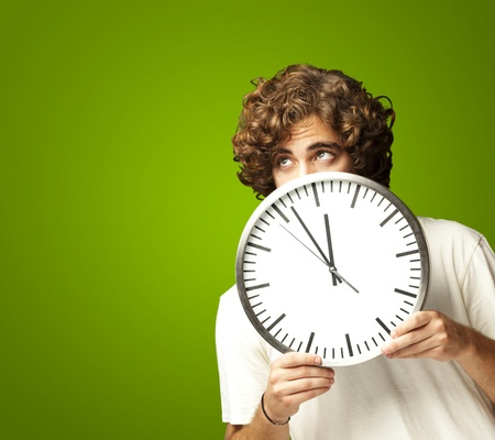 scared young man hidden behind a clock against a green background photo