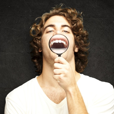 teeths: portrait of young man with magnifying glass showing his teeths against a vintage wall