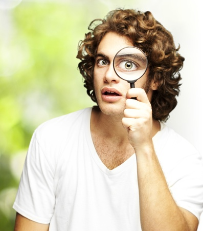 spy glass: portrait of young man looking through a magnifying glass against a nature background Stock Photo