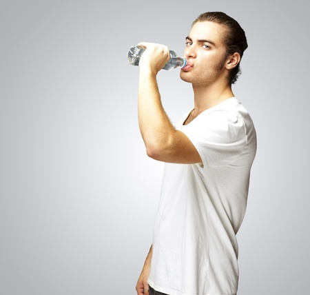 portrait of young man drinking water against a grey background Stock Photo