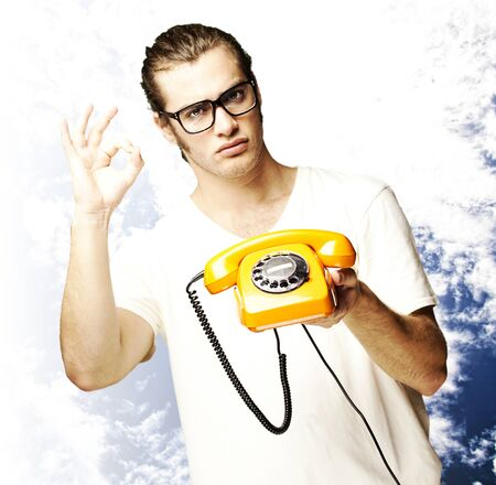 retro phone: portrait of young man holding a vintage telephone and gesturing against a cloudy sky background