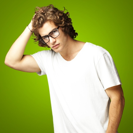 portrait of a handsome young man posing against a green background Stock Photo