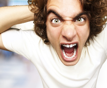 portrait of furious young man shouting against a abstract background Stock Photo - 13155978